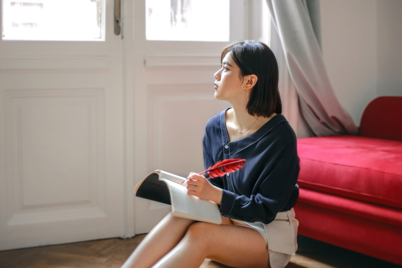 A young south-east Asian woman writes in a notebook with a red-feathered quill pen