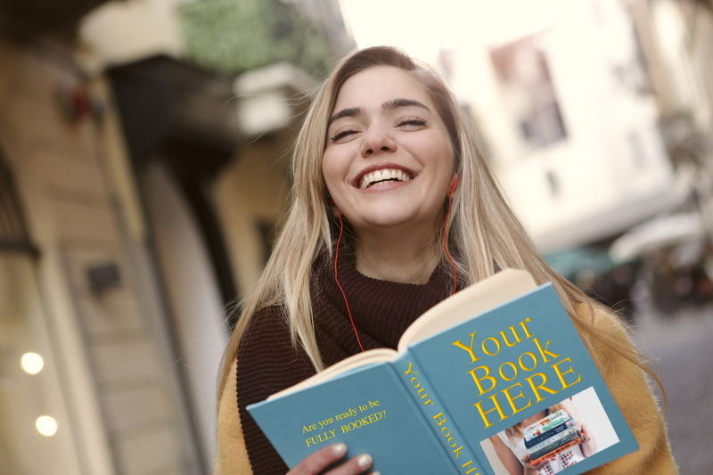 A laughing woman holds up a book titled Your Book Here